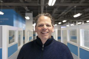 Jamie DeMaria, the new VP of Strategy at Pack Health, smiling at camera in blue pullover sweater